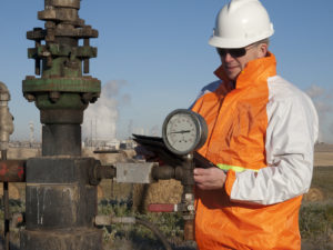 Oil worker engineer in safety gear inspects the well head of an oil well pumpjack. Agricultural seeting with petrochemical plant lining the horizon.